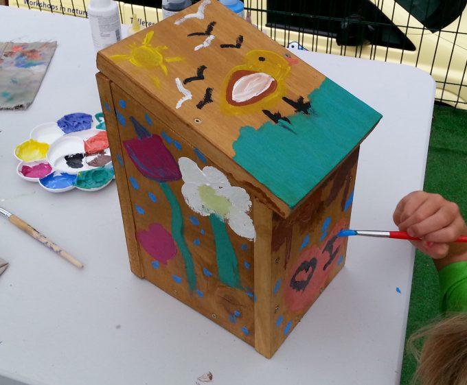 Niño pintando una caja nido