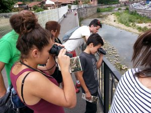 A group of people observe birds with their binoculars, next to the river Sella.