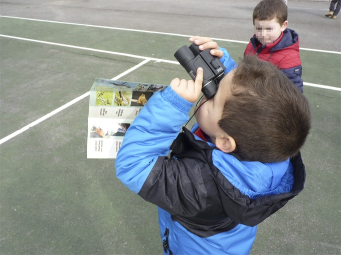 A kid looking through the binoculars