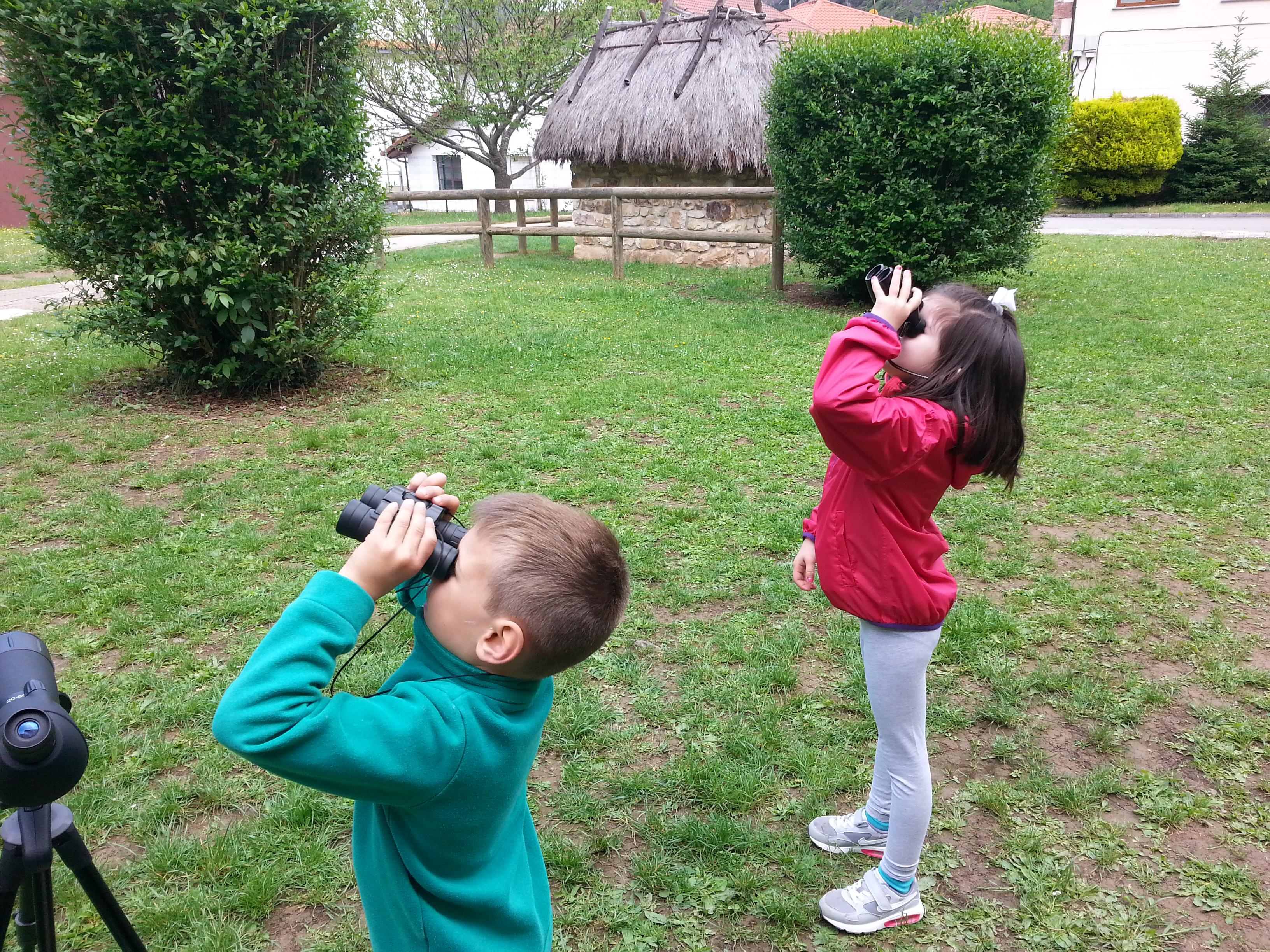 Niños mirando con prismáticos
