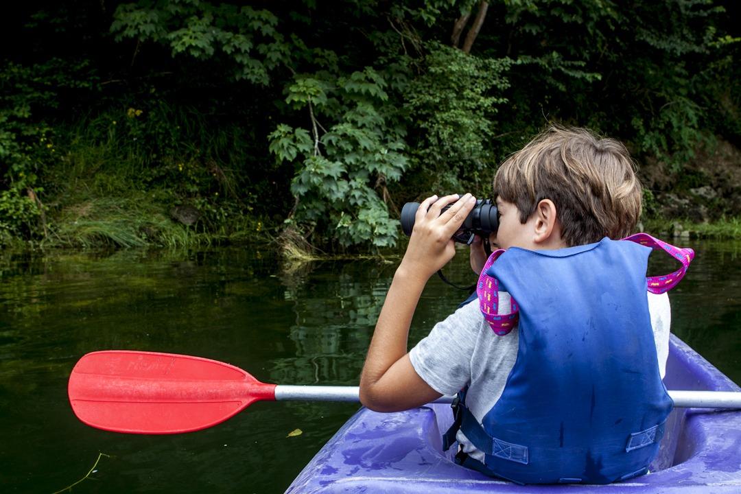 Niño observando la naturaleza desde la piragua.