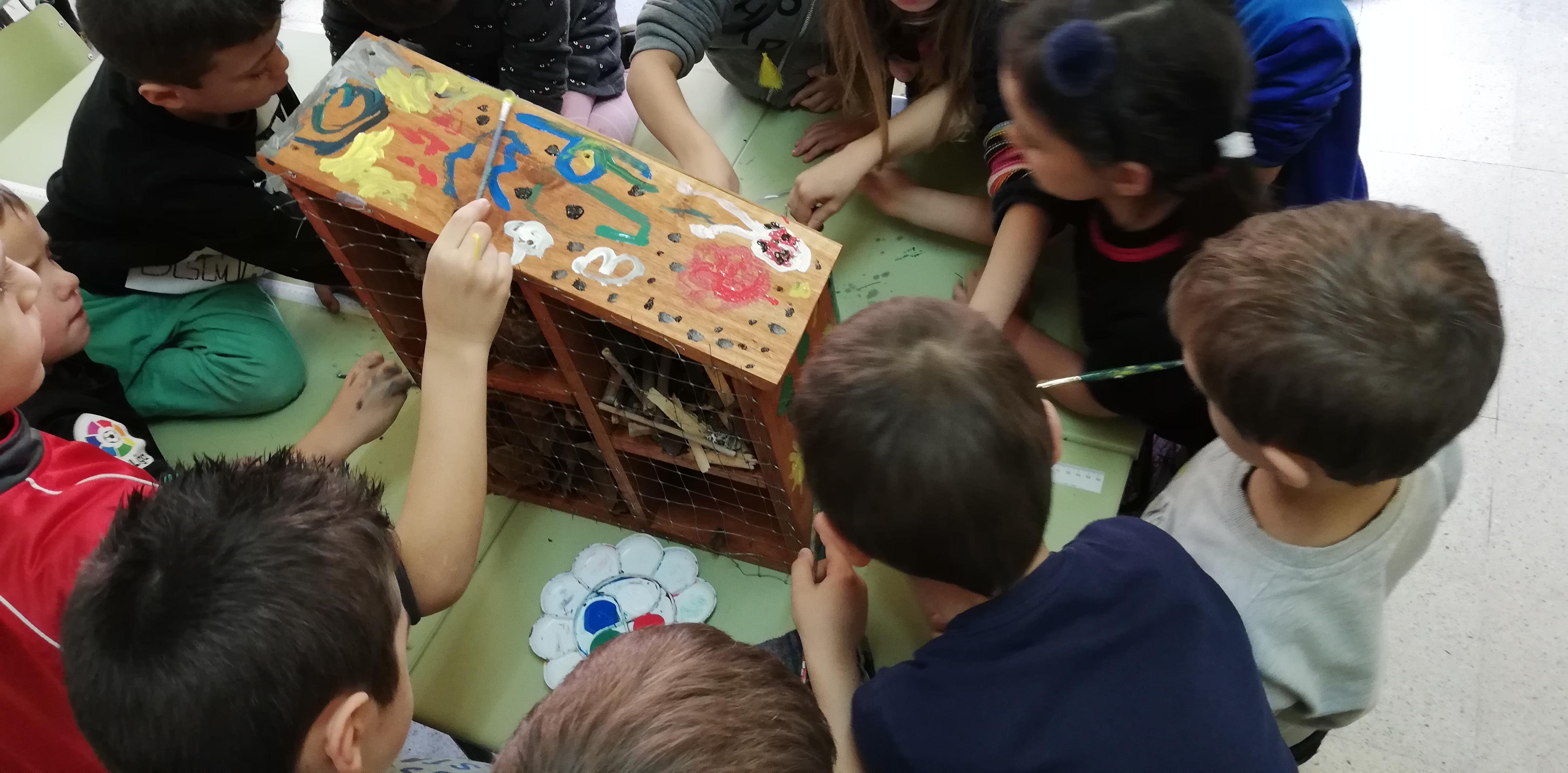 Un grupo de niñ@s pintando el hotel de insectos